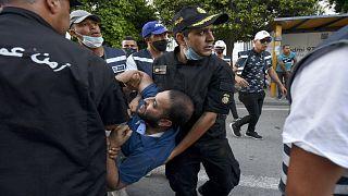 الشرطة التونسية تعتقل متظاهراً خلال احتجاجات ضد عنف الشرطة في شارع الحبيب بورقيبة بالعاصمة تونس، 12 حزيران/يونيو2021