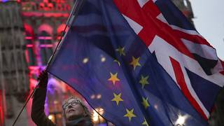 A woman holds up the British Union and the European Union flags together during an event in Brussels, Belgium on Jan. 30, 2020.