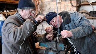 القبطان فالديمار شيزنيكي وميشال جيديناك يعملان على حبال لمركب شراعي في فناء مأوى للمشردين يديره كهنة كاثوليك في وارسو.