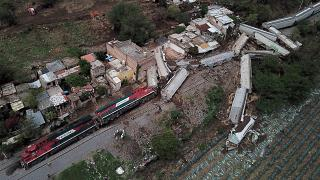 A freight train derailed and toppled onto houses alongside the tracks in western Mexico.