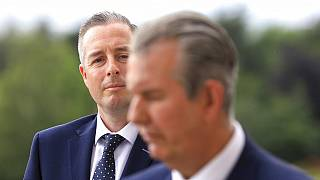 In this Tuesday, June 8, 2021 file photo, Democratic Unionist Party member Paul Givan, background, looks at party leader Edwin Poots during a press conference at Stormont.