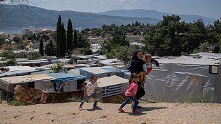 امرأة وأطفالها عند مخيم للاجئين في جزيرة ساموس اليونانية