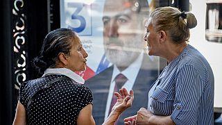 Deux femmes échangent à Erevan, devant une affiche de campagne, le 16 juin 2021, Arménie