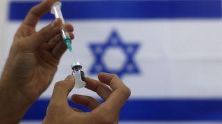 """جرعة من لقاح """"فايزرـ بوتنيك"""" وفي الخلفية العلم الإسرائيلي"""