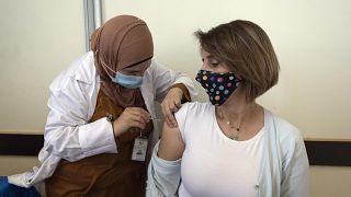 فلسطينية عاملة في القطاع الطبي تتلقى جرعة من لقاح فايزر/بيونتك