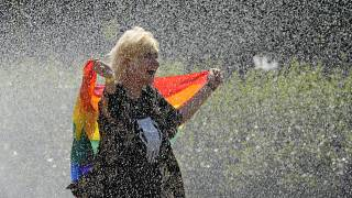 A woman with a rainbow flag cools off in a sprinkler ahead of the Equality Parade, the largest LGBT pride parade. Warsaw, Poland. June 19, 2021