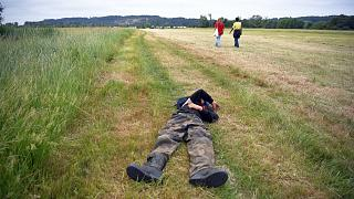 Two participants of an illegal rave party cross a field and one lies, in Redon, north-western France, on June 19, 2021, as French gendarmes intervene to disperse the event