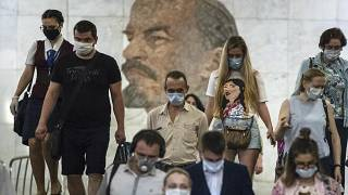 FILE: People wearing face masks walk through the subway, with a portrait of Soviet founder Vladimir Lenin in the background, in Moscow, Russia, June 10, 2021.