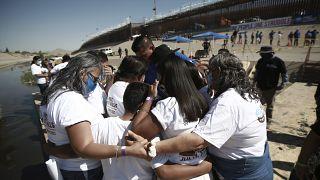 Miembros de una familia migrante se abrazan tras reencontrarse en la frontera