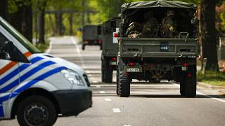 FILE - In this Friday, May 21, 2021 file photo, Belgian military ride in a convoy during a manhunt for an armed soldier in Maasmechelen, Belgium.