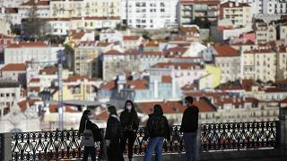 FILE - In this March 11, 2021 file photo, a group of young people wearing face masks chat at a viewpoint overlooking Lisbon's old center.
