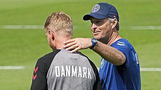 Denmark's captain Simon Kjaer, left, gets touched on the shoulder by Denmark's manager Kasper Hjulmand during a training session at the training ground in Helsingor, Denmark.