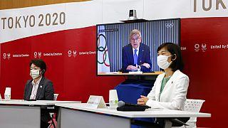 A Tokyo 2020 elnöke, Seiko Hashimoto (b), a japán olimpiai miniszter, Tamayo Marukawa (j) és az IOC elnöke, Thomas Bach egy képernyőn meeting közben.