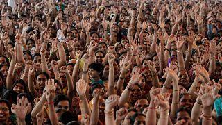 Hindistan'ın Ahmedabad kentinde yoga gurusu Baba Ramdev'i dinlerken ellerini kaldıran kadınlar (arşiv)