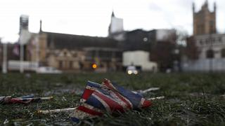 A British Union flag from Brexit day celebrations lies in the grass in front of the Palace of Westminster in London, early Saturday, Feb. 1, 2020.