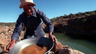 منقب للماس يغسل الحصى الذي أخذه من مجرى يمر عبر منجم نوبل دايموند في روستنبرج، جنوب إفريقيا.