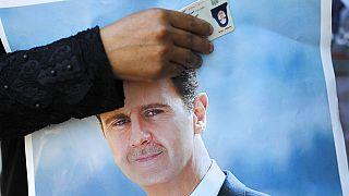 maggio 2020: una profuga siriana in Libano tiene in vista la sua carta d'identità su un poster di Basar al-Assad