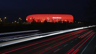 FILE - In this Monday, March 16, 2020 file photo, cars pass the illuminated 'Allianz Arena' soccer stadium in Munich, Germany.