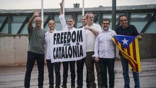Catalan leaders hold a banner and Catalan pro-independence flag outside Lledoners prison in Sant Joan de Vilatorrada, near Barcelona