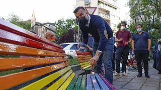 FILE - In this Friday, May 7, 2021 filer, Italian lawmaker Alessandro Zan paints a bench in the colors of the rainbow, in Milan, Italy.