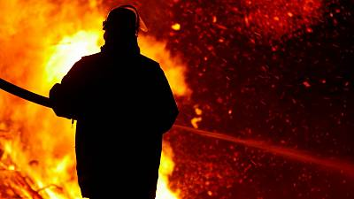 A firefighter stands in front of a blaze. New Augmented Reality technology is aiding firefighters in California.