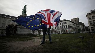 صورة أرشيفية لرجل يرفع علم الاتحاد الأوروبي وعلم بريطانيا قرب البرلمان الأوروبي في بروكسل