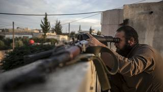 FILE: In this Thursday, Sept. 19, 2013 photo, a Syrian opposition fighter watches over as heavy fighting breaks out in in the Idlib province countryside, Syria