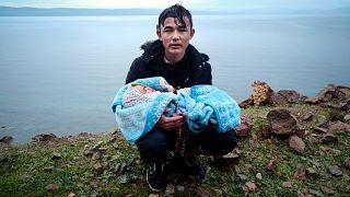 Kucağındaki bebekle Türkiye'den hareketle, Ege Denizi'ni geçerek Yunanistan'a ulaşan bir mülteci dinlenirken