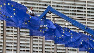 أعلام الاتحاد الأوروبي ومن خلفها مقر المفوضية الأوروبية في بروكسل