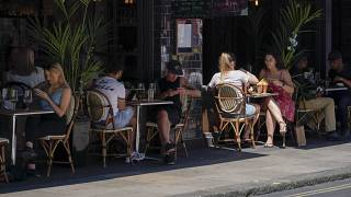 FILE: People sit at outdoor tables at a restaurant in Soho, in London, Monday, June 14, 2021.