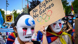 Tibetan and Uyghur activists hold placards and wear masks during a protest against Beijing 2022 Winter