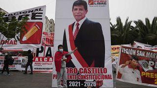 Un joven posa junto a un cartel gigante del candidato izquierdista Pedro Castillo en Lima, Perú.
