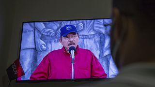 Un hombre sigue el discurso televisado del presidente de Nicaragua, Daniel Ortega, en su casa de Managua