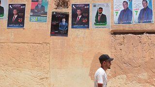رجل يمشي قرب معلقات انتخابية في عين وسارة (ولاية الجلفة) البعيدة عن العاصمة الجزائرية بنحو 190 كلم. 2021/06/10