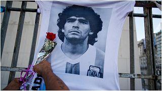 رجل يضع زهرة على قميص به صورة لنجم كرة القدم الراحل دييغو مارادونا-الأرجنتين
