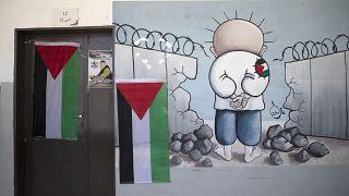 معلقة كاريكاتور للطفل الفلسطيني محمد حمايل توشح باب قسم مدرسي من بلدة بيتا في الضفة الغربية المحتلة.