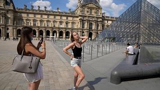 Two girls take pictures outside the Louvre Museum courtyard, in Paris, June 9, 2021 as France reopened its borders to foreign travellers.