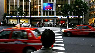 FILE: a Japanese man looks up at an electronic stock price board, in Tokyo, Aug. 17, 2007.