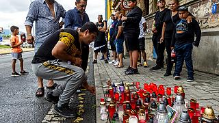 A man  lighting up candle Tuesday, June 22, 2021  in Teplice, Czech Republic, in the place where a Roma man died in an ambulance after a police action on Saturday, June 19.