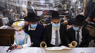 رجال وأطفال يهود أرثوذكس في كنيس مفصولة بأقسام بلاستيكية في بني براك، إسرائيل، الخميس 25 فبراير 2021.
