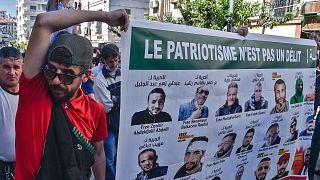 جزائريون يحملون لافتات عليها صور لنشطاء محتجزين في السجن، خلال مظاهرة مناهضة للحكومة في العاصمة الجزائر، 7 مايو 2021