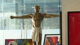 كاني ويست في صورة تمثال ذهبي للمسيح معروض للبيع في معرض فني