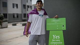Keilan Schembre, 29, who campaigns for the YES vote during a referendum in Gibraltar, poses for a portrait next a polling station in Gibraltar, Thursday, June, 24, 2021.