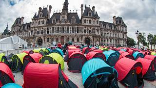 Homeless migrants sit in tents installed in front of the City Hall in Paris.