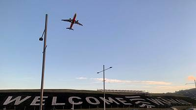 A giant sign painted near the main runway of the Wellington International Airport greets travellers returning home on April 19, 2021.