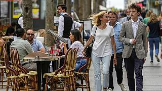 FILE: People walk at the Champs Elysees avenue in Paris, Thursday, June 17, 2021.