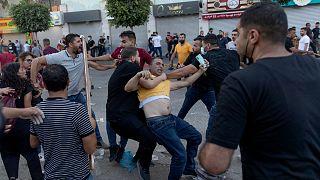 ضباط أمن فلسطينيون يرتدون ملابس مدنية يعتقلون متظاهرا خلال اشتباكات اندلعت في أعقاب مسيرة احتجاجية على مقتل الناقد الصريح للسلطة الفلسطينية نزار بنات، في رام الله.