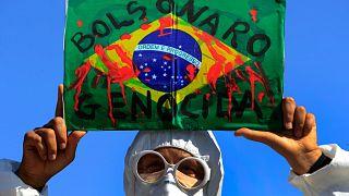 متظاهر يرفع صورة علم البرازيل مخضبا بالدم تعبيا عن احتجاج البرازيليين ضد سياسة بولسونارو الخاصة بمكافحة كوفيدـ19. 2021/05/26