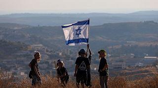 """أطفال المستوطنين الإسرائيليين يلوحون بالعلم الوطني بالقرب من مستوطنة """"بات عاين"""" في الضفة الغربية المحتلة، 21 يونيو 2021"""