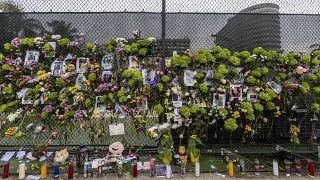 Flores y velas en honor de los desaparecidos junto a una valla cercana al edificio que se derrumbó parcialmente en Miami-Dade.